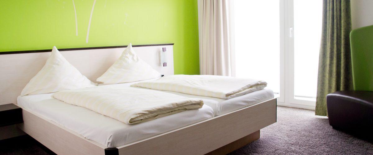 Lichtdurchflutetes Doppelzimmer mit einem Doppelbett vor grüner Wand