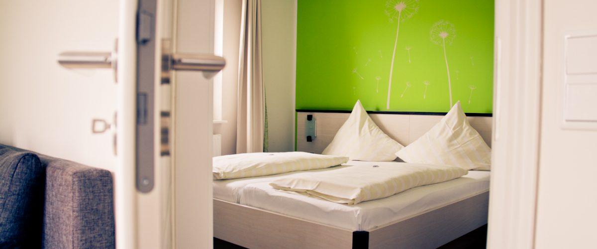 Appartement in Hotel Fauna - Doppelbett vor grüner Wand
