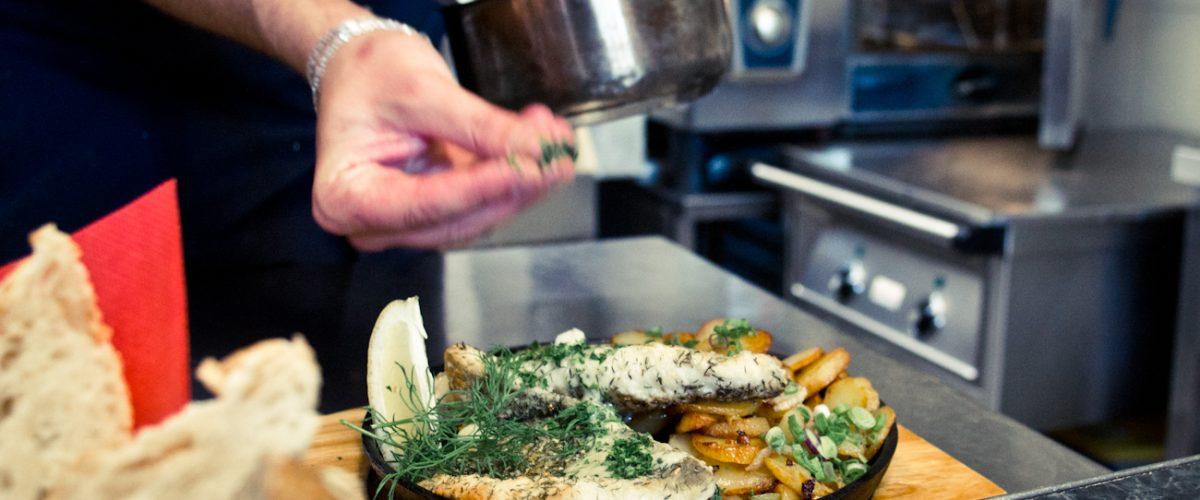 Koch bestreut Fischbratkartoffelgericht mit Kräutern
